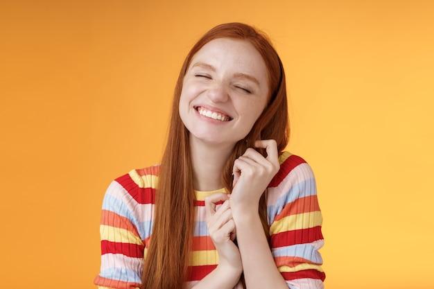 Szczęśliwa rozmarzona romantyczna młoda delikatna ruda dziewczyna fantazjująca tworząca historię miłosną wyobraźnia uśmiechnięta szeroko zachwycona zamykająca oczy dotykająca kosmyków włosów przywołująca miłe wspomnienie, stojąca na pomarańczowym tle.