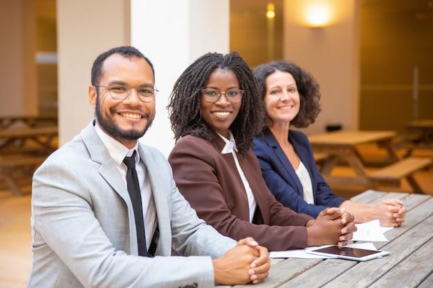 Szczęśliwa różnorodna biznes drużyna pozuje w ulicznej kawiarni