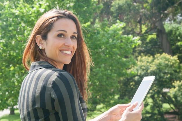 Szczęśliwa rozochocona biznesowa dama używa pastylkę