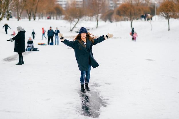 Szczęśliwa rozochocona długa z włosami brunetka jedzie lód ślad na zamarzniętym jeziorze w zima dniu.