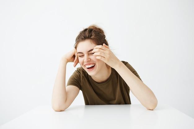 Szczęśliwa rozochocona młoda piękna kobieta z babeczką uśmiecha się roześmianego obsiadanie przy stołem nad białym tłem.