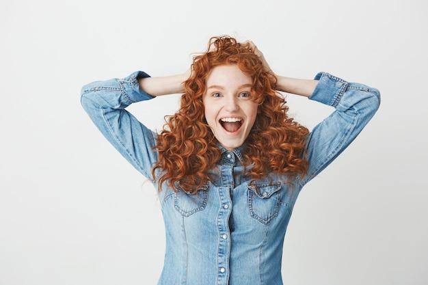 Szczęśliwa rozochocona rudzielec dziewczyna uśmiecha się cieszący się z otwartym usta.