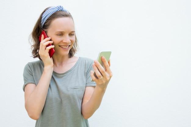 Szczęśliwa ruchliwie młoda kobieta używa dwa telefonu komórkowego