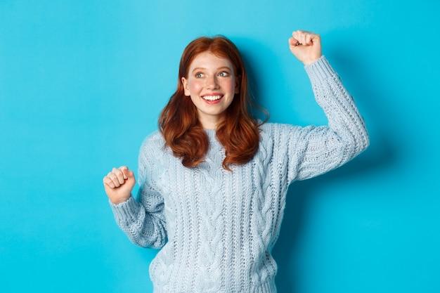 Szczęśliwa ruda dziewczyna kibicuje drużynie, wiwatuje z podniesioną ręką i uśmiecha się, świętuje zwycięstwo lub sukces, stojąc na niebieskim tle.