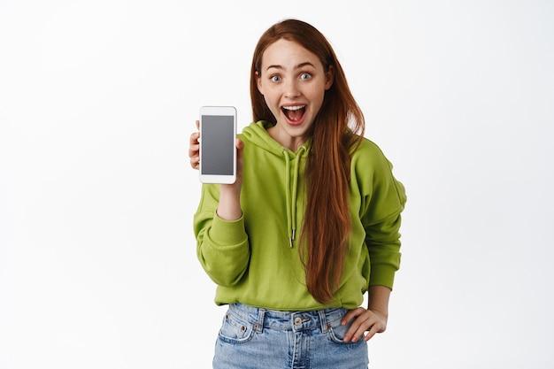 Szczęśliwa ruda dziewczyna, pokazująca ekran smartfona, pusty telefon i patrząca zdumiona, sprawdzająca aplikację stojącą na białym tle.