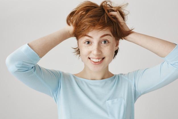 Szczęśliwa ruda dziewczyna pozuje na białej ścianie