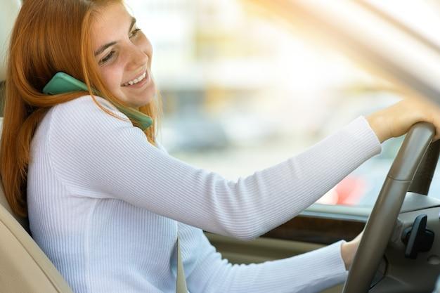 Szczęśliwa ruda dziewczyna rozmawia jej telefon komórkowy za kierownicą podczas prowadzenia samochodu