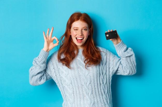 Szczęśliwa ruda dziewczyna w swetrze pokazuje kartę kredytową i dobrze znak, polecając ofertę banku, stojąc na niebieskim tle.