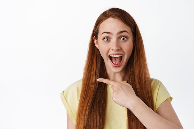 Szczęśliwa ruda dziewczyna wskazująca palcem w lewo stojąca zdumiona na białym