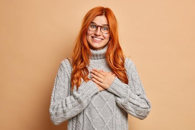 Szczęśliwa ruda kobieta trzyma ręce na klatce piersiowej, czyni gest wdzięczności, uśmiecha się radośnie, nosi dzianinowy szary sweter.