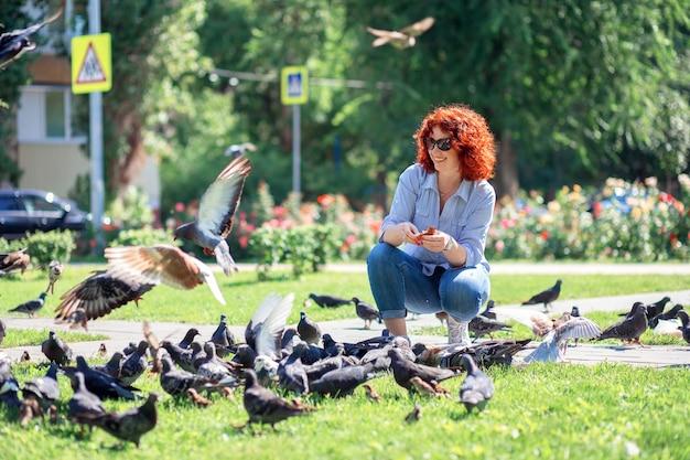 Szczęśliwa ruda kobieta w parku miejskim karmi gołębie chlebem