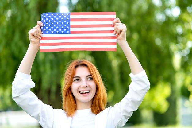 Szczęśliwa rudowłosa dziewczyna pozuje z flagą narodową usa nad głową stojąc na świeżym powietrzu w parku latem.