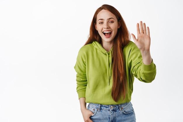 Szczęśliwa rudowłosa kobieta mówi cześć, machając podniesioną ręką w geście powitania, uśmiechając się przyjaźnie, stojąc na białym