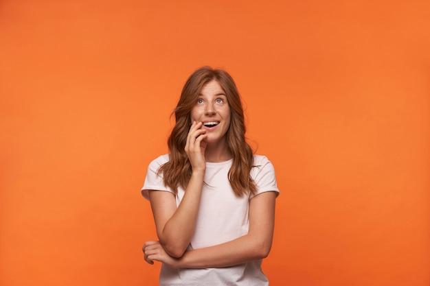 Szczęśliwa rudowłosa młoda kobieta z lokami, trzymając rękę na brodzie i patrząc w górę radośnie, odizolowana, na sobie ubranie