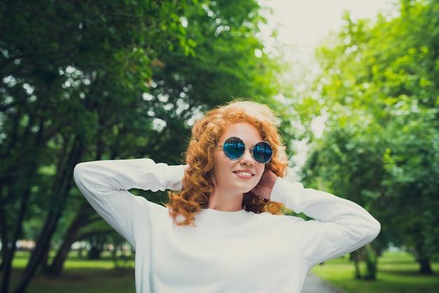 Szczęśliwa rudzielec młoda kobieta w okularach przeciwsłonecznych