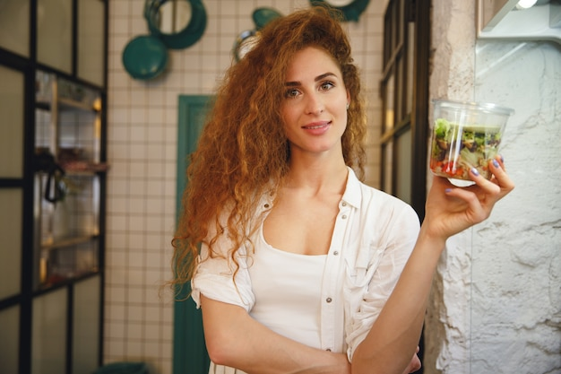 Szczęśliwa rudzielec młodej damy pozycja w kawiarni podczas gdy trzymający sałatki.