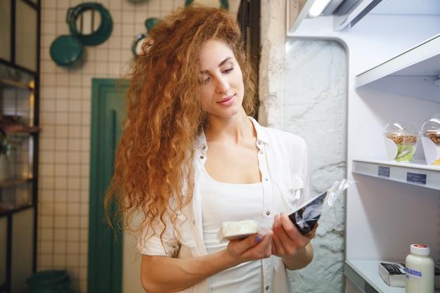 Szczęśliwa rudzielec młodej damy pozycja w kawiarni podczas gdy trzymający ser