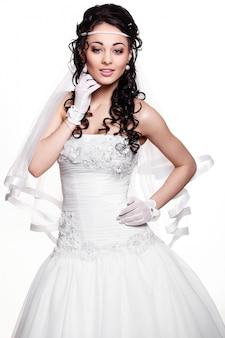 Szczęśliwa seksowna piękna panny młodej brunetki dziewczyna w białej ślubnej sukni z fryzurą i jaskrawym makeup na białym tle