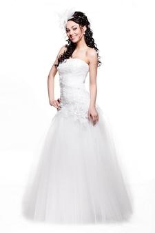 Szczęśliwa seksowna piękna panny młodej brunetki kobieta w białej ślubnej sukni z fryzurą i jaskrawym makeup pełnej długości w stylu retro