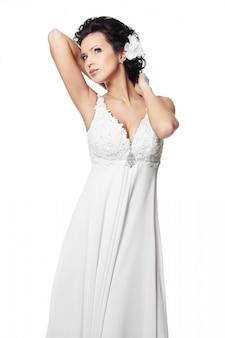 Szczęśliwa seksowna piękna panny młodej brunetki kobieta w białej ślubnej sukni z fryzurą i jaskrawym makeup z kwiatem w włosy odizolowywającym na bielu