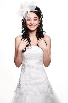 Szczęśliwa seksowna piękna panny młodej brunetki kobieta w białej ślubnej sukni z fryzurą i jaskrawym makijażem