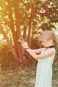 Szczęśliwa siedmioletnia dziewczynka fotografuje letni naturalny krajobraz za pomocą aparatu, korzystając z podglądu na żywo. dzieci adoptują hobby rodziców. letnia edukacja dzieci na wakacjach. migotać