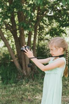Szczęśliwa siedmioletnia dziewczynka fotografuje letni naturalny krajobraz za pomocą aparatu, korzystając z podglądu na żywo. dzieci adoptują hobby rodziców. letnia edukacja dzieci na wakacjach