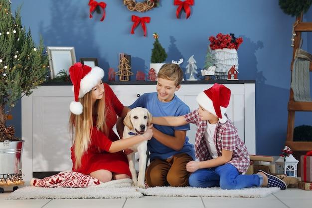 Szczęśliwa siostra i bracia bawią się z psem na podłodze w urządzonej sali bożonarodzeniowej