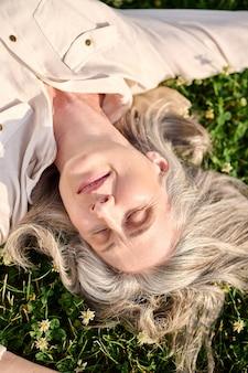 Szczęśliwa siwowłosa kobieta leżąca na trawie