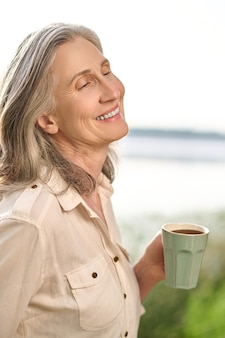 Szczęśliwa siwowłosa kobieta z filiżanką na zewnątrz