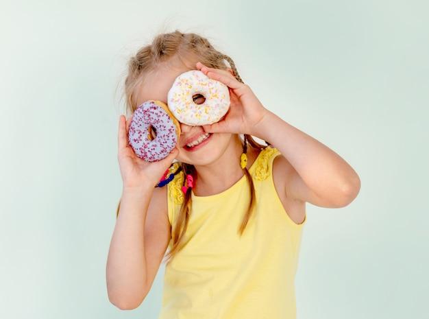 Szczęśliwa śliczna blond dziewczyna trzyma dwa pączka na ona oczy