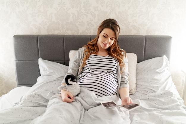 Szczęśliwa śliczna brunetka leży w łóżku, trzymając zabawkę pingwina i patrząc na zdjęcie usg swojego dziecka.