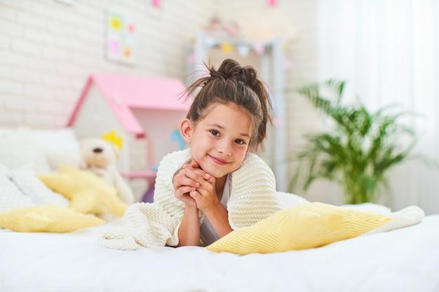 Szczęśliwa śliczna dziewczyna kłama na łóżku w jej dziecko pokoju z koc