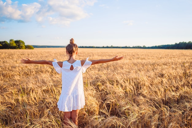 Szczęśliwa śliczna dziewczyna w polu pszenicy na zewnątrz