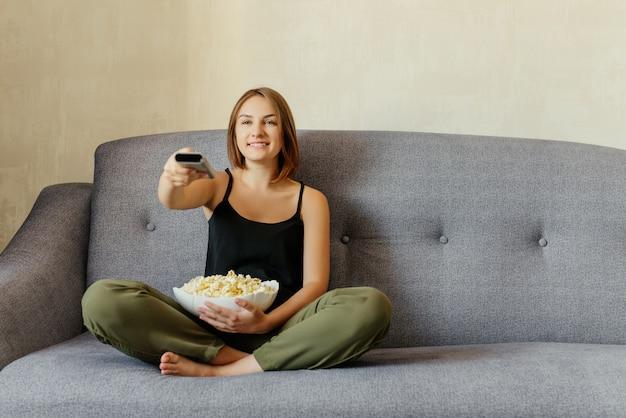 Szczęśliwa śliczna dziewczyna z obsiadaniem na szarej kanapie, jedzeniem popcornu, oglądaniem telewizji. wewnątrz. czas relaksu.