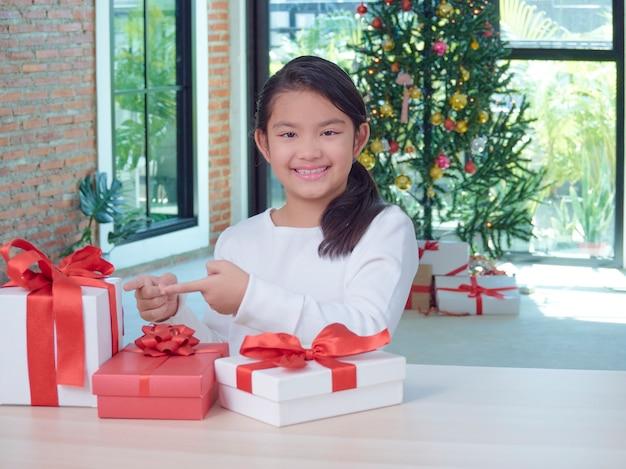 Szczęśliwa śliczna dziewczyna z pudełka na prezenty w domu z świątecznymi dekoracjami.