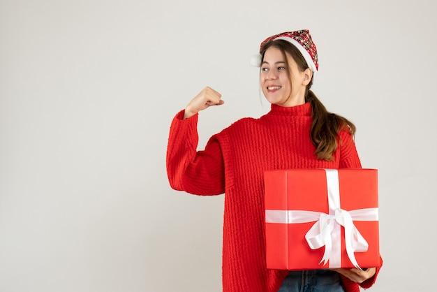 Szczęśliwa śliczna dziewczyna z santa hat trzyma ciężki prezent pokazując jej siłę stojącą na białym tle