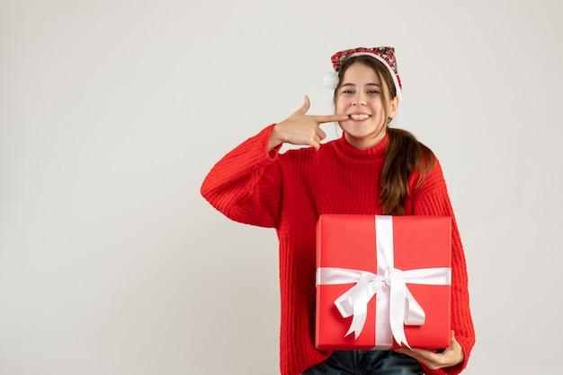 Szczęśliwa śliczna dziewczyna z santa hat trzyma ciężki prezent, wskazując na jej zęby stojąc na białym