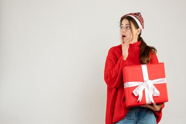 Szczęśliwa śliczna dziewczyna z santa hat trzyma prezent kładąc rękę na jej brodzie stojąc na białym