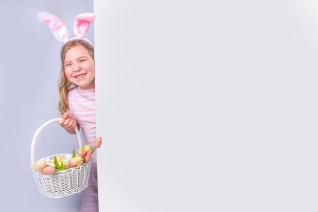 Szczęśliwa śliczna dziewczyna z uszami królika. tło wielkanoc kartkę z życzeniami. z pisankami i wiosennym kwiatem w koszu