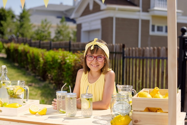 Szczęśliwa śliczna dziewczyna z zębatym uśmiechem sprzedaje świeżą fajną domową lemoniadę w gorący letni dzień, stojąc przy drewnianym straganie na zewnątrz