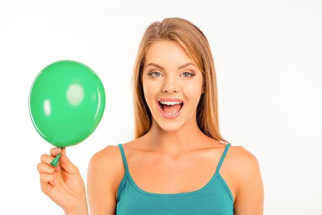 Szczęśliwa śliczna dziewczyna z zielonym balonem, uśmiechając się