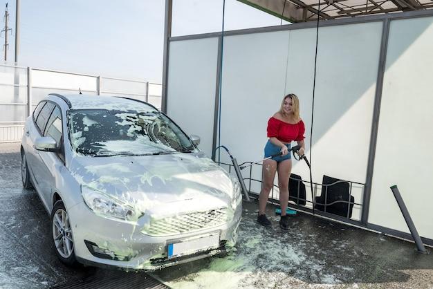 Szczęśliwa śliczna kobieta czyści swój samochód pistoletem na wodę pod wysokim ciśnieniem
