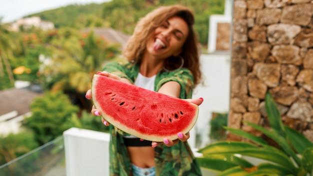 Szczęśliwa śliczna kobieta trzyma arbuza z falistymi włosami.