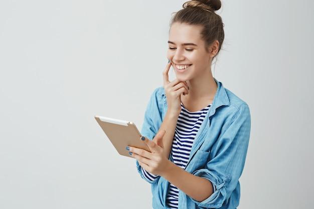 Szczęśliwą śliczną kobietą wygrywa bilety do kinowej loterii online patrząc zadowolony zadowolony cyfrowy wyświetlacz tabletu ekran uśmiecha się rozbawiony.
