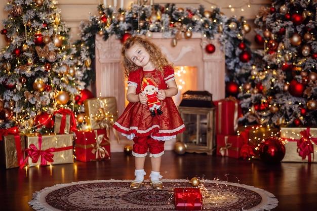Szczęśliwa śliczna mała blondynka z długimi włosami w czerwonej sukience, czekając na boże narodzenie