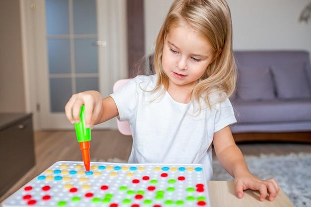 Szczęśliwa śliczna mała blondynki dziewczyna siedzi przy stołem w domu bawić się z zabawkarskim śrubokrętem i multicolor śrubami. wczesna edukacja.