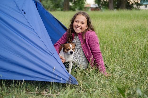 Szczęśliwa śliczna mała dziewczynka grać z psem chihuahua w namiocie. szczęśliwa rodzinna wycieczka latem. podróżuj ze zwierzętami. ciesz się czasem spędzonym razem. zdjęcie wysokiej jakości