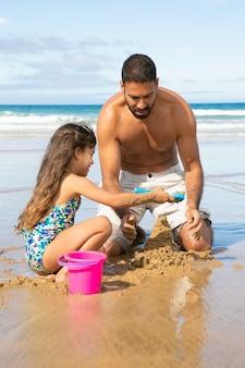 Szczęśliwa śliczna mała dziewczynka i jej tata budują zamek z piasku na plaży, siedząc na mokrym piasku, ciesząc się wakacjami