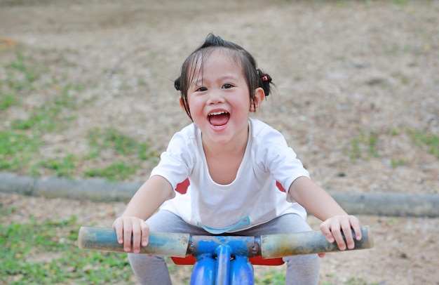 Szczęśliwa śliczna mała dziewczynka na saw w parku